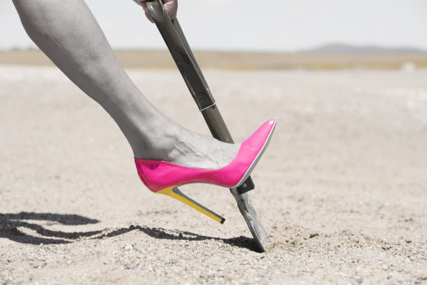 woman in pink high heel digging with shovel in sand